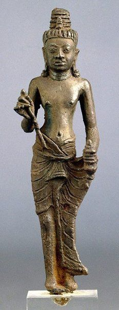 Name of Deity: Maitreya Country of Origin: Cambodia Date: 8th century Medium: Bronze Alloy  Mudra: Maitreya holds a lotus flower in her right hand while grasping her robe in the other hand.