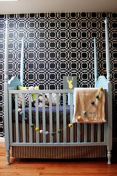 Hang the felt ball garland on the baby cot.