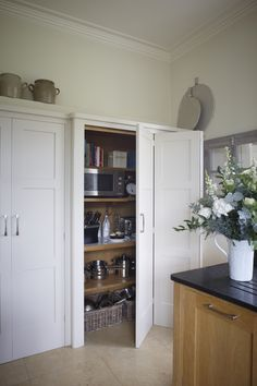 Tall larder cupboard along a wall in white with bi-fold doors. Storage for appliances, pots and pans and cookery books. Kitchen designed by Giles Slater for Figura