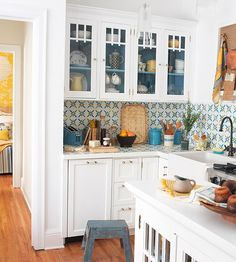 Cabinet backs are painted a lovely shade of blue and the backsplash is fun and unique! Very charming kitchen full of personality!