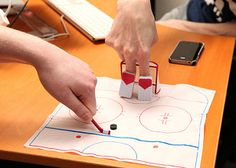 """Finger Hockey Desktop Office Game    Why get bruised and bloodied playing the treacherous sport of hockey on an ice rink when you can do it right on your desktop? This is a game that the millions of rabid hockey fans around the globe will love. Kit includes a set of finger """"goalie"""" pads, net, hockey stick, puck, skating rink playing mat, and a 32-page rule book on Finger Hockey."""