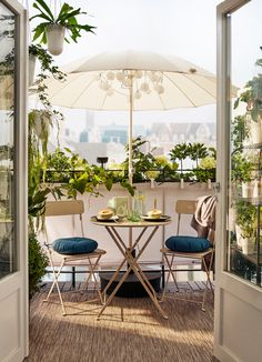 Balcony with beige table and chairs under a parasol, surrounded by plants.