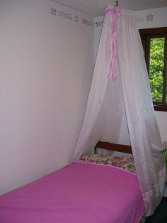 The pink princess canopy bed, made from curtains that were folded up in the closet, a cut hanger, $1 roll of wired ribbon, and some ribbons stolen from yesterday's wedding. She really wanted a pink princess room. This is as far as I was willing to go in that direction, and she is very happy with it.