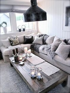 Love this look!: tons of comfy pillows and blankets on a corner sofa, with slightly rustic wood coffee table
