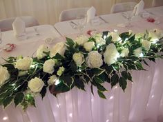Top table flower arrangement in beutiful artificial leaves and flowers with tiny diamond pins in the flower heads and LED lights underlighting the arrangement.