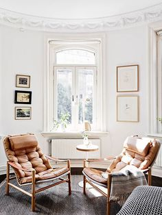 Matching brown lounge chairs + white walls in a sunny spot.