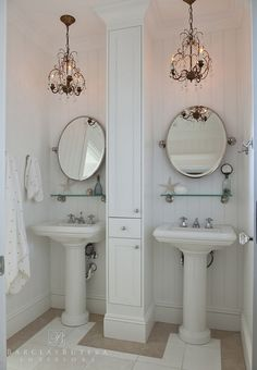 This bathroom features board and batten wall paneling and pedestal sinks with a built-in cabinet in the center Wall paint color is Satin White Valspar