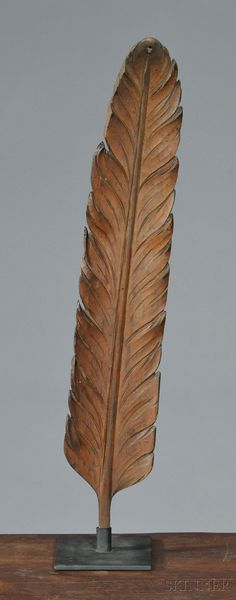 Carved Pine Feather, America, 19th century, carved in the round, with stand, (imperfections), overall ht. 25 1/4, wd. 4 1/2 in.      Provenance:  Peter Carswell Antiques, Strafford, New Hampshire.      There's a small hole drilled on the tip, several old losses to some of the feather edges.