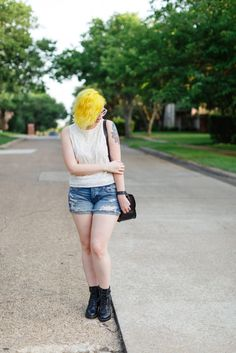 Casual summer outfit with distressed denim shorts, a feminine tank top and heeled combat booties