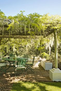 """Create secluded and romantic seating by constructing a square pergola, draped with white wisteria. Traditional bistro seating completes the look.  Like this? Then you'll love  [link url=""""http://www.houseandgarden.co.uk/interiors/kitchen""""]Kitchen Ideas[/link]"""