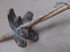 iran-khorasan-tribal-hand-carved-wooden-drop-spindle. Circa: 1900 – 1920 Size: 3″ long propellers – 11″ long original rod IRAN – KHORASAN – Ethnic hand carved wooden drop spindle. Carved motifs are under the propellers. The dark patina indicates that it has good age and used for a long time.
