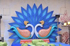 Area decorated with two peacock figures attached to a substantial blue flower-shaped base. Maroon Curtains, Swag Curtains, Wedding Flower Decorations, Stage Decorations, Engagement Stage Decoration, Decoration For Ganpati, Arab Wedding, Green Cushions, Flower Stands