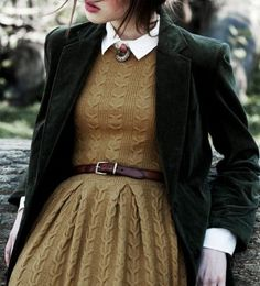 Cable knit sweater dress with pleated skirt, leather belt, white Oxford shirt, blazer, vintage brooch