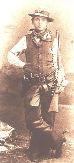 Cowboy with all the gear, Boss of the Plains hat, vest, chaps, Winchester, spurs, Colt revolver