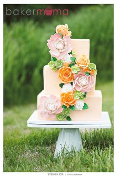 Ivory white wedding cake with green, pink, and orange floral cascade