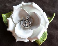 Here's a large, beautiful white enamel rose with 6 rhinestones in the center. This bright white open rose has two green leaves and a stem as well. Ab...  #black #flowers #green #leaves #white