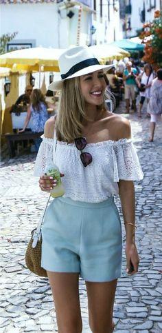 Tendência verão: Como estilizar o short de alfaiataria. Chapéu fedora branco, blusa de renda com decote ombro a ombro, short azul.