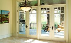 floor to ceiling windows and double french doors directly to patio.