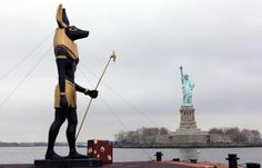 7 Ton Replica statue of the Egyptian God Anubis passes by the Statue of Liberty in New York