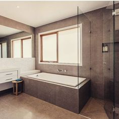 White inbuilt bathtub into charcoal tiled walls. White vanity, semi frameless shower screen. Project by - @brentbuilders #taps #interiordesign #bathroom #australia #architecture #bathroomdesign #bathroomcollective Visit our website for more www.bathroomcollective.com.au