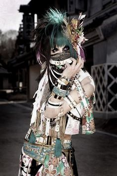 """Visual kei (ヴィジュアル系, vijuaru kei. , lit. """"visual style"""" or """"visual system"""") is a movement among Japanese musicians, that is characterized by the use of varying levels of make-up, elaborate hair styles and flamboyant costumes, often, but not always, coupled with androgynous aesthetics."""