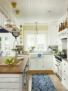 Shiplap, butcher block, subway tile, farm sink, the light fixtures, an island, bright colors, lots of natural light, wood floors, floor runner, modern but with vintage flair  ... I'm IN LOVE with this kitchen!
