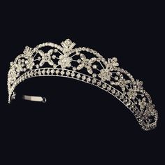 This charming tiara features a floral pattern of silver plated flowers covered in rhinestones and enchanting Swarovski crystals to give this piece its royal look. It is lined with circular rhinestones