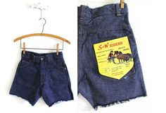 Amazing little cutoffs from the early 1960s!  Made by S-W Riders in a heavy, dark denim. High waisted with front snap button and metal zipper closure. These were likely longer and then cut for some odd reason. They are new old store stock and have never been worn. The cuts are slightly lopsided.  Excellent condition! Some stitching along the left side seam has come undone a bit. Still very sturdy with the other stitch in tact. These shorts have been washed by me. Fits best on a modern size…