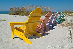 Colorfully painted wooden lawn chairs on a sunny beach.