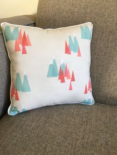 Mountains in aqua and burnt orange decorate this modern beige pillow. This is the perfect pillow for a nature or mountain themed childs room! PRODUCT DETAILS: * Made of cotton fabric * Backed with coordinating beige fabric * Trimmed in oyster piping * Measures approximately 11 x 11
