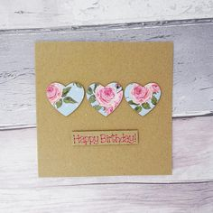 Handmade Happy Birthday card with three hearts featuring a vintage floral print. This pink rose heart birthday card would be a lovely card for a wife, sister or friend who loves the vintage or shabby chic style for their birthday. The pattern on the hearts can be chosen from the drop-down menu, and in the feature photo included a blue background with white polka dots and pink roses and rose buds. The hearts are mounted on 3D foam. The sentiment on this floral birthday card is added in pink…