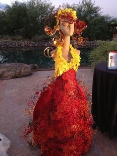 https://flic.kr/p/hjCYNe | Spanish Tendrils: The contrast of hard and soft | Tendrils and spirals of copper, gold, red and brown wires create a lace effect over the red satin dress. Flaring panels are embellished with metal lace. Yellow silk cymbidium petals over the bodice and down the back of the skirt add bursts of color. Harsh metals manipulated and caressed create soft, flowing movement.