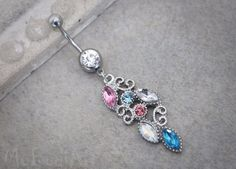 This gorgeous peacock tail dangle belly button ring in silver features a high luster clear crystal cut gem with a multicolor jeweled peacock tail dangle charm. Sparkle your way into style this summer