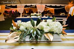 I love these centerpieces & how southern they are with the magnolia leaves. Deep greens & gold really went well with the navy colors chosen by the bride | Rosemary Beach Wedding  | Woodland Fields Photography #woodlandfieldsphotography