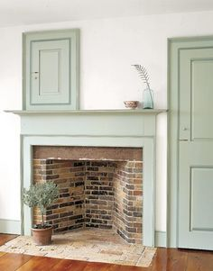 Pale Soft Green Paint used on the Fireplace Wood  Surround and Doors. A potted Topiary dresses the Hearth and a Blue Tint Bottle with a Feather dresses the Mantle.
