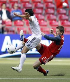 Toronto FC's Terry Dunfield (R) kicks Vancouver Whitecaps' John Thorrington in the groin during the first half of the Amway Canadian Championship soccer final in Vancouver, British Columbia May 16, 2012. REUTERS-Ben Nelms