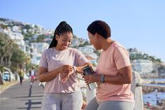 Black fitness friends resting after a workout on a seaside promenade outdoors in summer. They are smiling and wearing fitness activewear, one of them uses an activity tracker Fitness Friends, Friends Workout, Black Fitness, Seaside, Activewear, Smart Watch, Outdoors, The Unit, Stock Photos