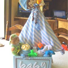 Sail boat baby shower gift with everything a baby needs for a bath including bath toys and cupcakes made out of wash cloths and bath towels.