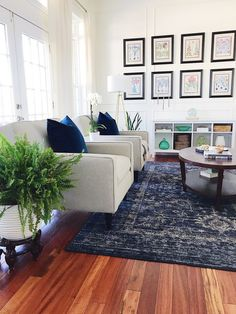 Make Your Home Feel More Cozy - blue and white coastal style living room with blue vintage rug and botanical gallery wall
