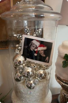 Christmas apothecary jars with ornaments, snow, & family photos