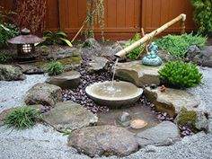 Napa Valley fieldstones surround this water feature. We built a small fountain surrounded by gravel and dwarf evergreens.To keep costs down, we fabricated the bamboo fountain and sourced the granite basin.
