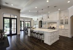 open plan. dark floors. white kitchen.