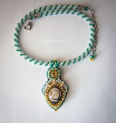 Pendant with agate Glazkov Pendant is made in white and green and gold colors. The central part of the pendant takes ocellar agate, located at the top of the Czech rhinestones yellow. The product is collected on a tow of white and green matte beads Czech company Preciosa. $ 12.5