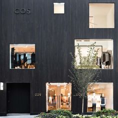 Fashion brand COS has opened its first Canadian store, concealing a minimal-looking interior behind a blackened cedar facade