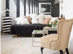 Karmelowy fotel uszak i karmelowe poduszki na czarnej sofie w salonie z czarno-białą fototapetą na ścianie (26260)