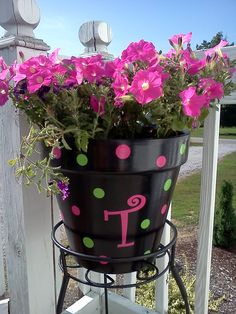 Spray painted pot with vinly letter and polka dots. Add modge podge over letters and polka dots. :)