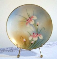 Nippon Floral Porcelain Cabinet Plate. Hand painted with tall, pink and white flowers and buds against an oramge and blue-blushed background. The plate is accented with a gold rim.
