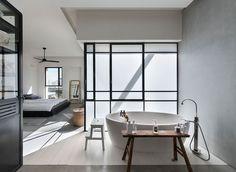 Une salle de bains ouverte au design minimaliste fait partie de la chambre principale
