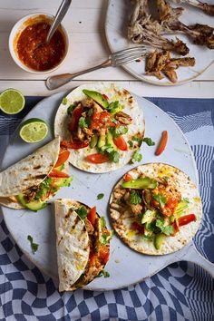 Serveer de tortilla's met de pulled chicken, de tomaten-avocadosalade en de chilisaus. Eetsmakelijk!