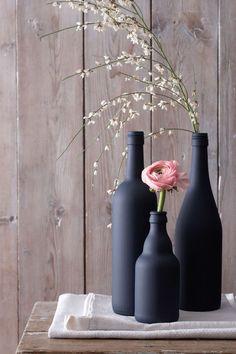 De simples bouteilles deviennent des vases déco, une fois peintes avec une belle couleur. On a choisi ici un petit pot de gris noir de chez Little Greene qui suffit pour peindre 2 ou 3 bouteilles. On aime le fini volontairement mat de la peinture qui permet d'obtenir un rendu plus chic.   Pot échantillon de 60ml à 7,50 euros, Little Greene sur papierpeintdirect.com